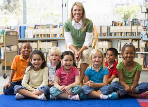 children with their teacher smiling